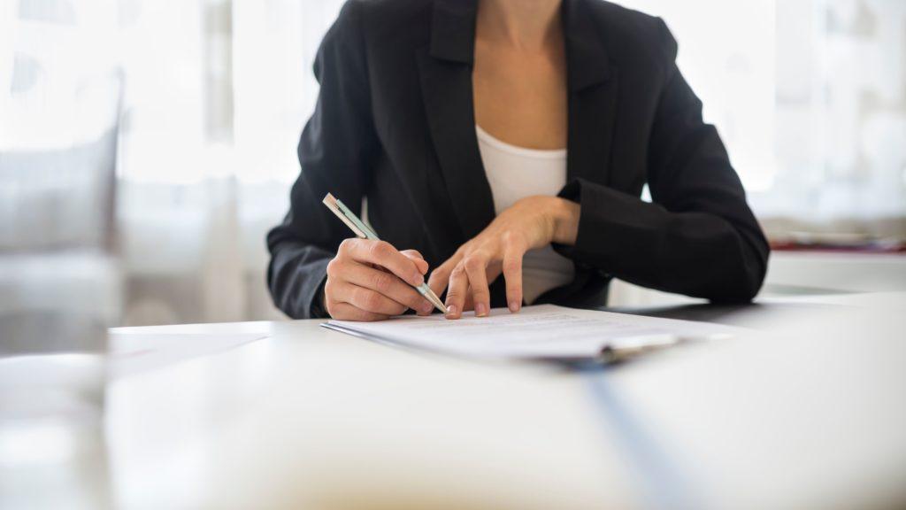 kobieta podpisująca dokumenty - protokół z konsultacji